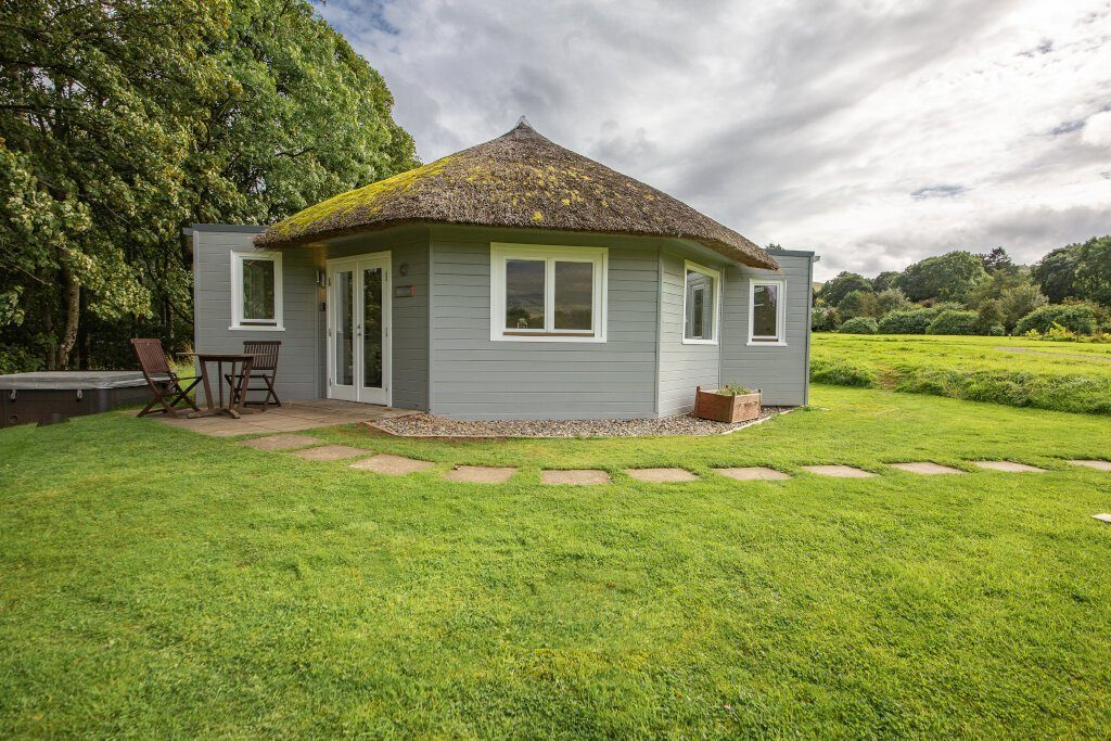 Willow cottage surrounded by garden and trees