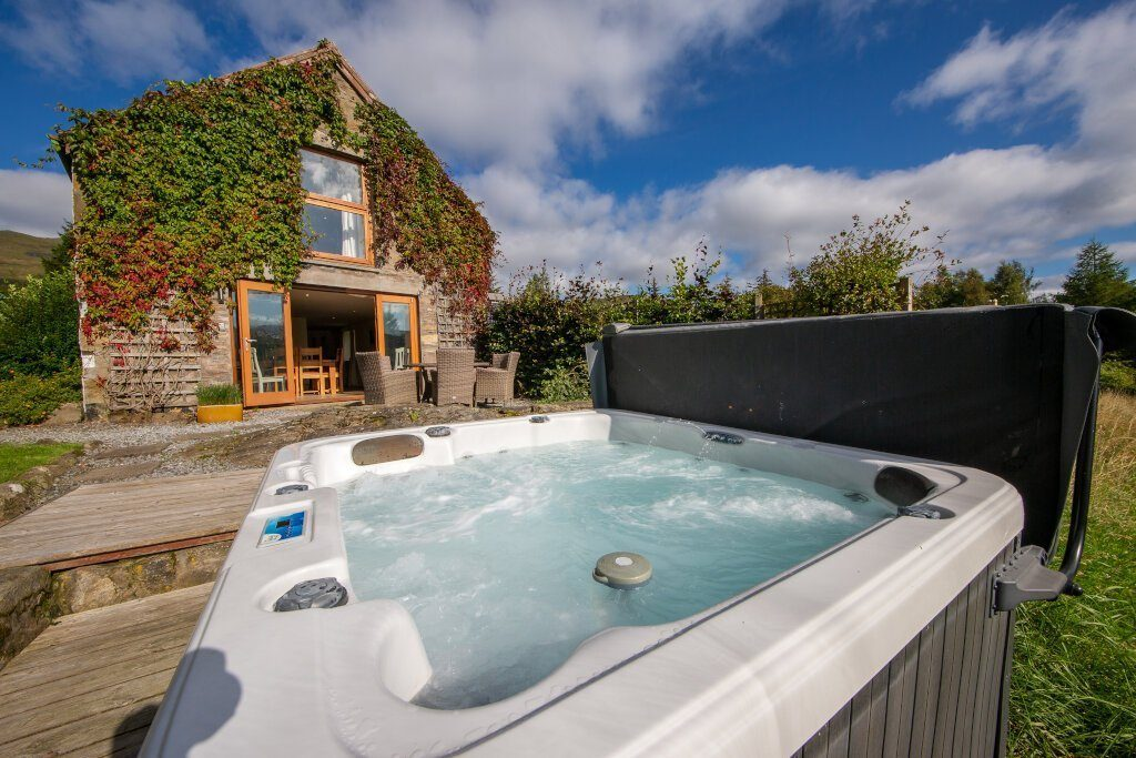 barn lodge hot tub with barn lodge in background with wall plants covering building